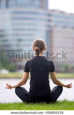 Young office woman sitting cross legged on the street in front of modern office building, meditating, practicing yoga Easy Pose, Sukhasana, asana for meditation, pranayama, breathing, back view - stock photo