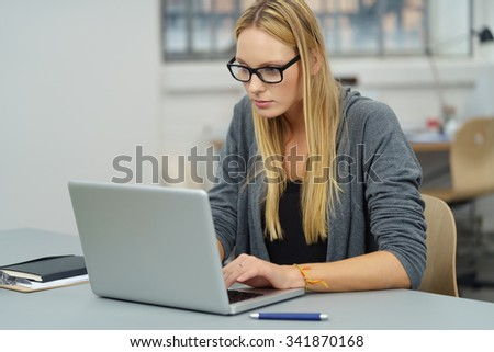 Young Office Woman Working Something on her Laptop Computer at her Desk Seriously - stock photo