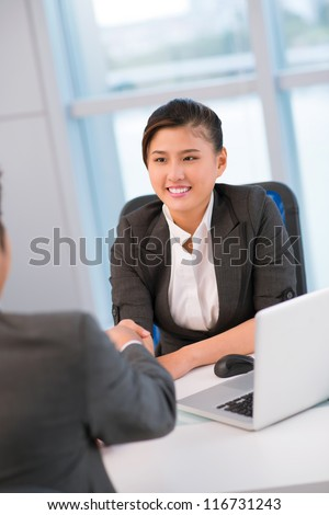 Young office worker greeting a potential candidate for vacant position or a new partner