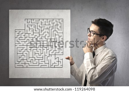 Young office worker holding a cardboard with a drawn maze - stock photo