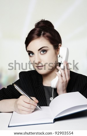 young office worker on the phone taking notes - stock photo