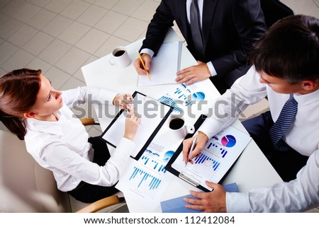 Young office workers discussing papers at meeting - stock photo