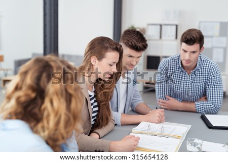 Young Office Workers in a Meeting Inside the Office, Reviewing the Compiled Documents on Top the Table - stock photo