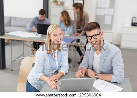 Young Office Workers Sitting at the Table with Laptop Computer, Looking at the Camera with Toothy Smiles.