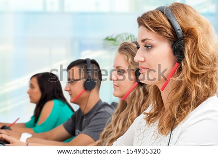 Young office workers with headsets giving customer service. - stock photo