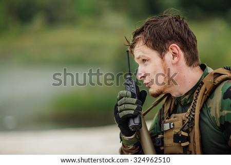 young officer holds a radio station, and give orders subdivision - stock photo