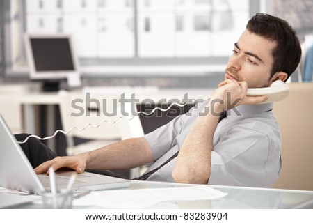 Young officer working in bright office, using laptop, talking on phone.? - stock photo