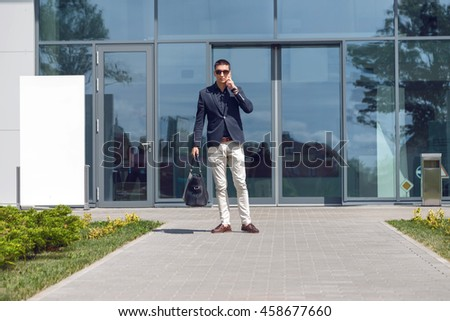Young official man expert calling via cell telephone while standing outdoors near modern glass building, young male employer talking on mobile phone - stock photo