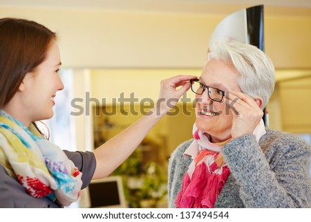 Young optician advising a senior woman for buying new glasses - stock photo