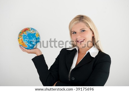 Young optimistic business woman in a suit holding a globe