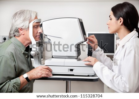 Young optometrist performing visual field test with an advance equipment - stock photo