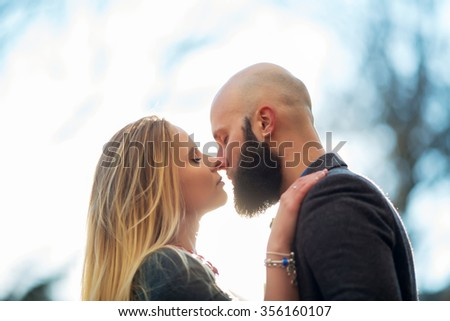 Young outdoor fashion portrait of beautiful couple kissing on the street