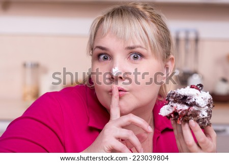 Young overweight woman wanting to eat secretly big cake - stock photo