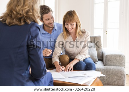 Young owners couple signing a contract for house investment. - stock photo