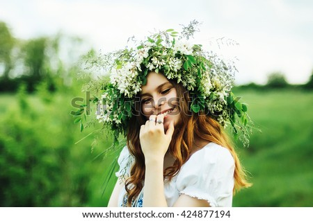 Young pagan Slavic girl conduct ceremony on Midsummer. Beauti girl dressed in a white blouse with embroidery, denim shorts, boots with grass Acacia wreath on his head against the background of nature - stock photo