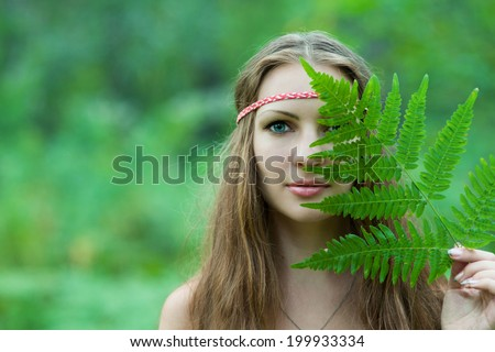 Young pagan Slavic girl with fern leaf - stock photo