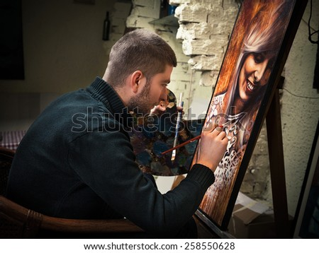 Young painter at his art studio, working on an oil painting portrait. - stock photo