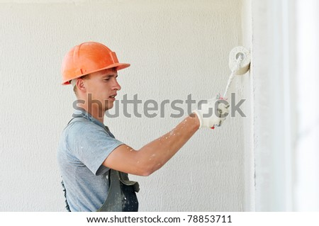 Young painting facade builder worker with roller at thermal insulation works - stock photo