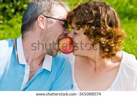 young pair bites apple - stock photo