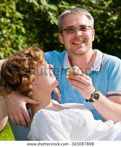young pair bites apple, sitting on a grass - stock photo