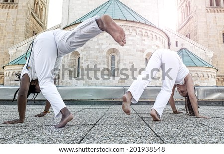 Young pair capoeira partners performing kicks outdoor - stock photo