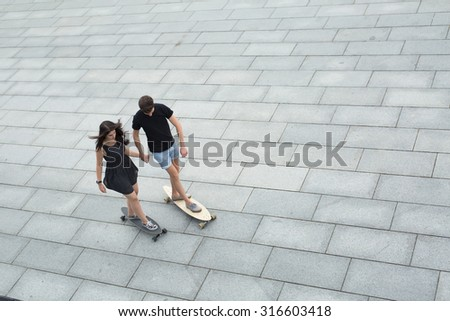 Young pair of stylish teenagers ride longboards