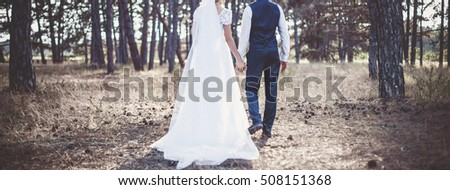 Young pair walking in forest in the wedding day