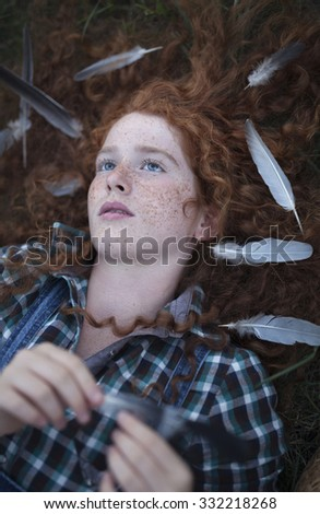 Young pale ginger girl with blue eyes and freckles in a blue plaid shirt, lying in the grass with feathers in her hair. Holding one feather and plays with him, looking up - stock photo