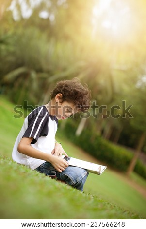 Young pan asian boy enjoying his reading book in outdoor park at sun down - stock photo