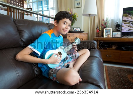 Young pan asian boy practicing on his blue ukulele in a home environment - stock photo