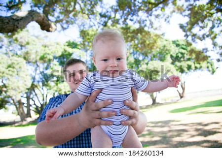 Young parent at the park with baby son.