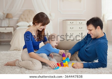 Young parents and cute son play building kit sitting on a carpet in children room - stock photo