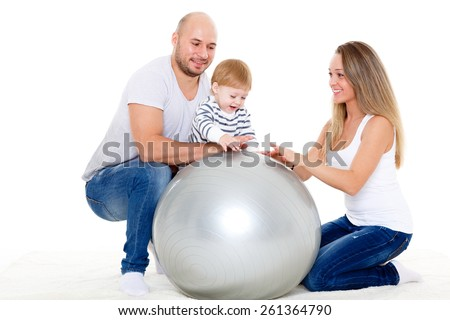 Young parents and sweet small baby with fitness ball on a white background. Healthy family. - stock photo