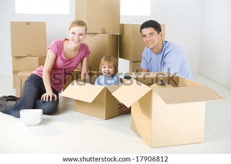 Young parents and their daughter sitting beside cardboard boxes. Young girl sitting in box. They're smiling and looking at camera. - stock photo