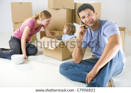Young parents and their daughter sitting beside cardboard boxes. Young girl sitting in box. They're smiling. A man talking by cellphone and looking at camera. Focused on man.