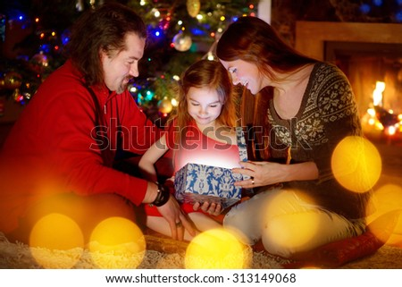 Young parents and their little daughter opening a magical Christmas gift by a Christmas tree in cozy living room in winter - stock photo