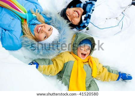 young parents and their son wearing warm winter clothes lie on the snow