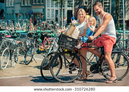 Young parents cycling with their little daughter along the streets of Amsterdam - stock photo