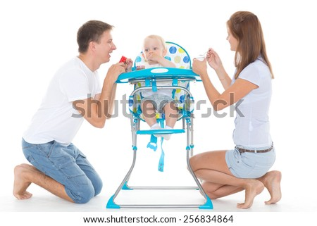 Young parents feed  baby on a white background. Happy family. - stock photo