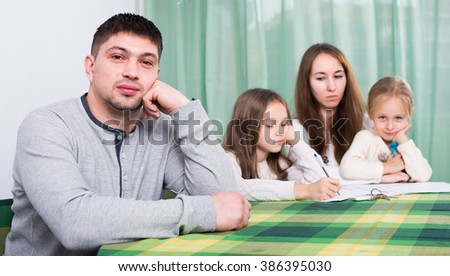 Young parents having quarrel about documents in front of children in  apartment  - stock photo