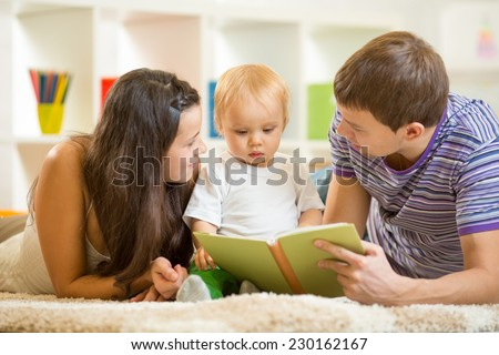 Young parents mom and dad reading children book to baby son
