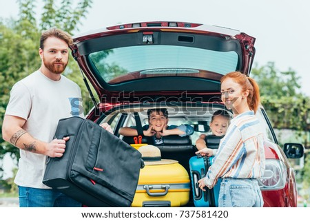 young parents packing luggage in trunk of car with kids looking from backseats