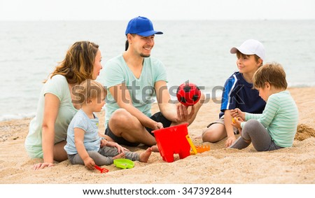 Young parents playing and talking with her three children on the beach - stock photo