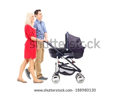 Young parents pushing a baby stroller isolated on white background - stock photo