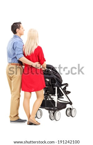 Young parents pushing a baby stroller isolated on white background, rear view - stock photo