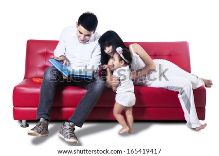 Young parents read the book to their baby - isolated on white background