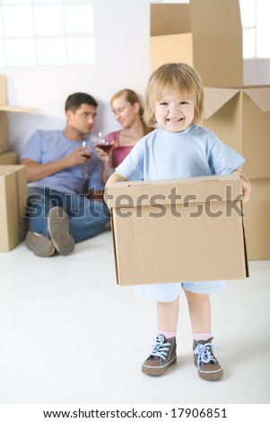 Young parents sitting beside cardboard boxes and drinking wine. Theirs daughter standing in frond and holding box. She's looking at camera. - stock photo