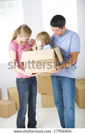 Young parents standing between cardboard boxes. They're holding one box with their daughter. Front view.