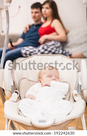 Young parents watchin TV while their baby sleeping in his cradle - stock photo