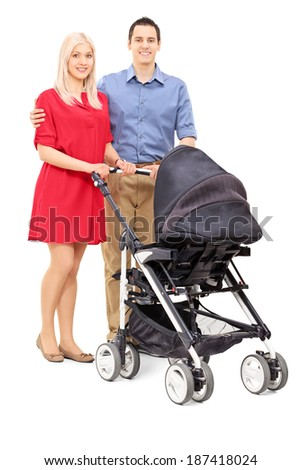 Young parents with a baby stroller posing isolated on white background - stock photo